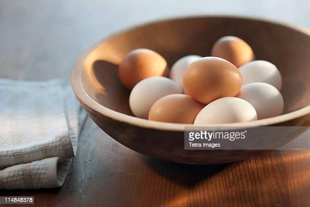 bowl of raw eggs on table - ei bruin stockfoto's en -beelden