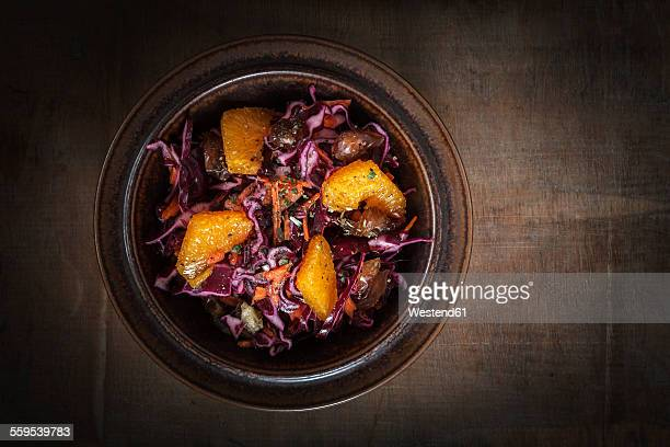Bowl of red cabbage salad with orange slices, carrots and dates