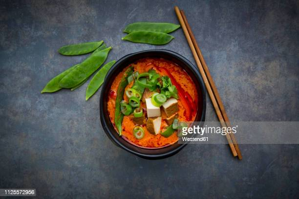 bowl of red thai curry with snow peas, carrots, bell pepper, spring onions and smoked tofu - curry stock pictures, royalty-free photos & images