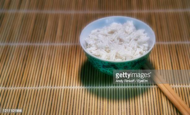 bowl of rice and chopsticks - andy rinkoff stock pictures, royalty-free photos & images
