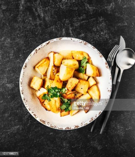 bowl of roasted potatoes on black background - ローストポテト ストックフォトと画像
