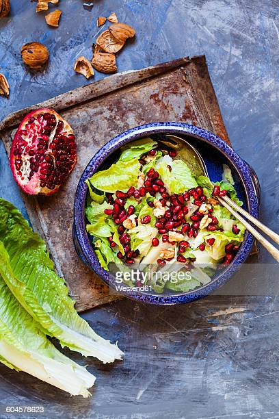 Bowl of Romaine lettuce with walnuts, pomegranate dressing and seed