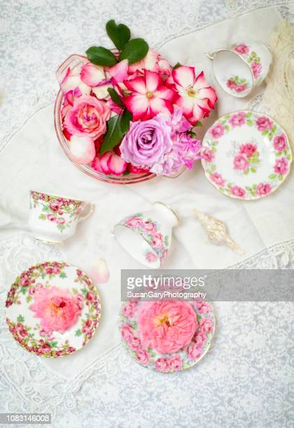 bowl of roses and vintage tea cups - doily stock photos and pictures