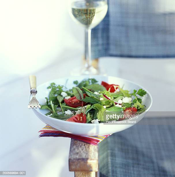 Bowl of Salad and glass of wine of the arm of a garden chair