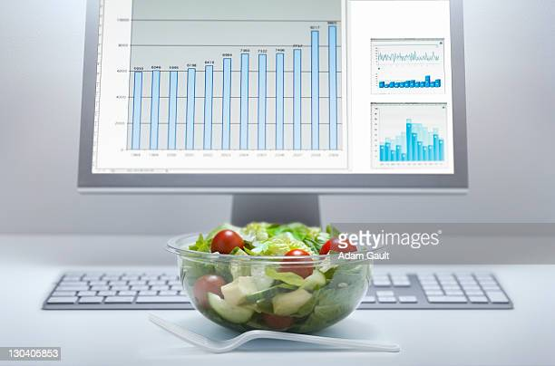 bowl of salad at computer desk - salad bowl stock pictures, royalty-free photos & images