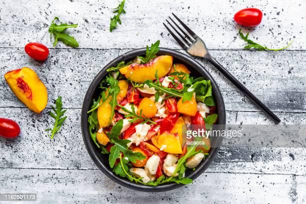 bowl of salad with nectarines, rocket, tomatoes, mozarella - salad stock-fotos und bilder