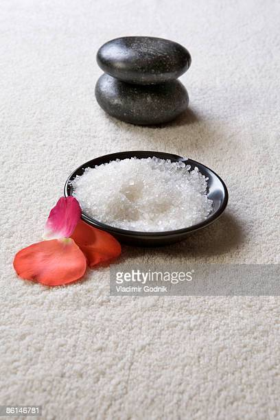 A bowl of sea salt with a pestle and rose petals