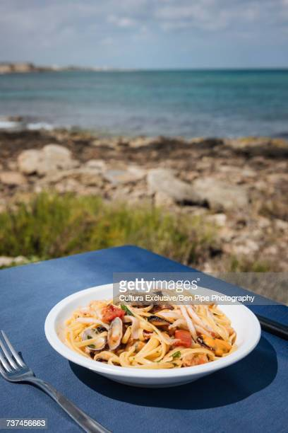 Bowl of seafood pasta on restaurant table at coast, Puglia, Italy