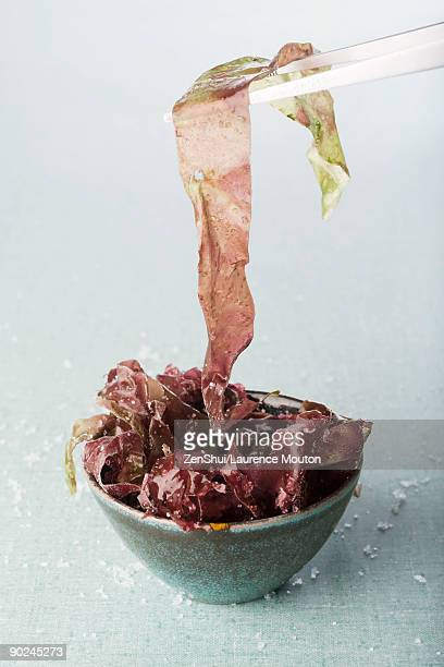 bowl of seaweed, chopsticks picking up piece - seaweed stock pictures, royalty-free photos & images