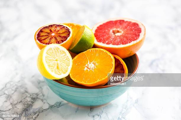 bowl of sliced citrus fruits - fruit bowl stock pictures, royalty-free photos & images