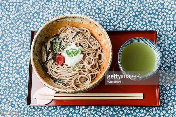 Bowl of Soba noodles on red lacquer plate and bowl of green tea