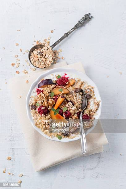 Bowl of soured milk with quinoa, fruit muesli, plums and raspberries