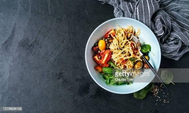bowl of spaghetti with basil, tomatoes and olives on black background - italian food stock pictures, royalty-free photos & images