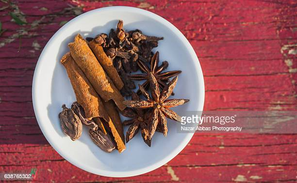 bowl of spices against red background. - garam masala stock photos and pictures