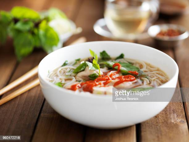 bowl of spicy vietnamese beef pho with sriracha sauce