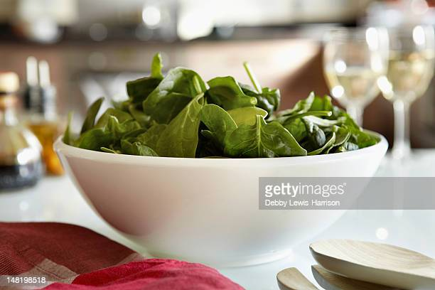Bowl of spinach salad on kitchen table