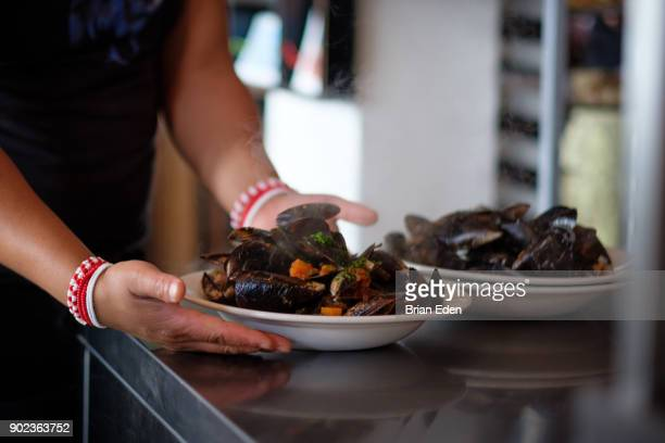 A bowl of steamed mussels is served at a restaurant