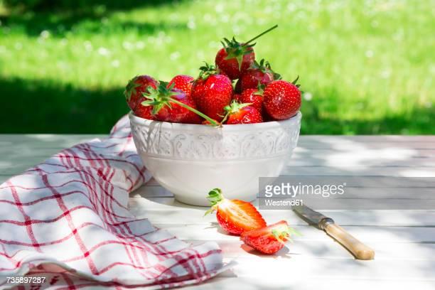bowl of strawberries, knife and kitchen towel on garden table - trapo de cocina fotografías e imágenes de stock