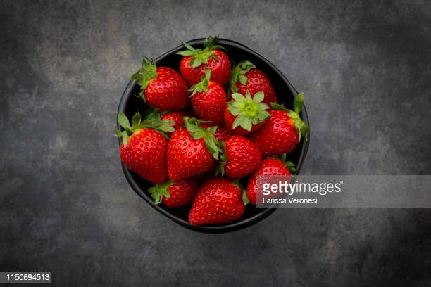bowl of strawberries on dark concrete - larissa veronesi fotografías e imágenes de stock