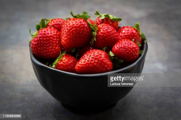 Bowl of strawberries on dark concrete