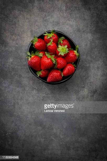 bowl of strawberries on dark concrete - larissa veronesi stock-fotos und bilder