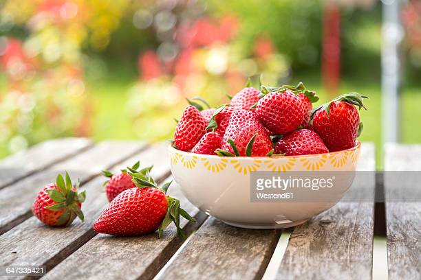 bowl of strawberries on wooden garden table - strawberry stock pictures, royalty-free photos & images