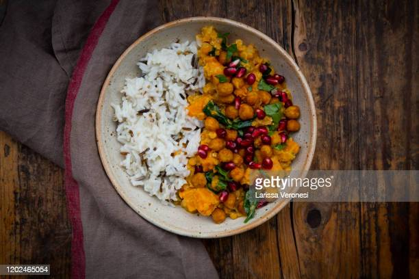bowl of sweet potato lentil curry with basmati rice - spinach stock pictures, royalty-free photos & images
