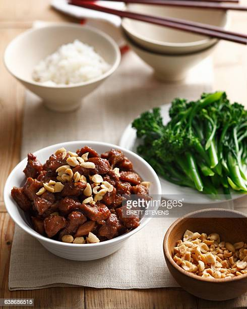 Bowl of Thai style pork with broccolini, peanuts and jasmine rice