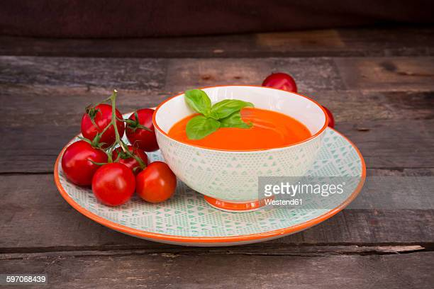 Bowl of tomato cream soup garnished with basil leaves