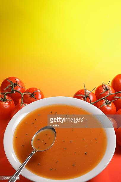 A bowl of tomato cream soup near piles of tomatoes