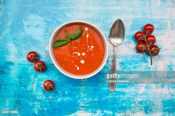 bowl of tomato soup on blue surface - tomato soup stock photos and pictures
