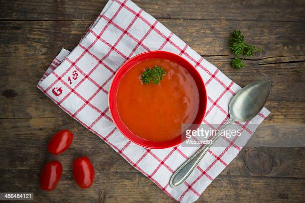 Bowl of tomato soup on kitchen towel and wooden table