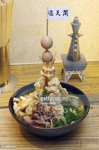 A bowl of 'Tower Curry Udon' noodles and a model of the Tsutenkaku tower are seen at a restaurant inside ShinImamiya Station of Nankai Electric...