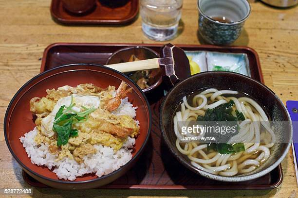 A bowl of Udon noodle soup and shrimp tempura over rice at a restaurant in Tokyo