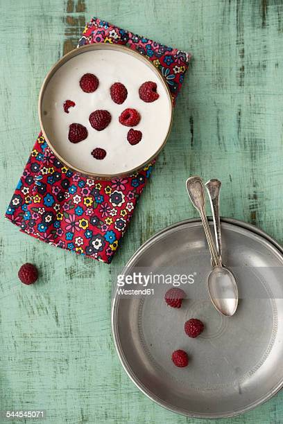 Bowl of vanilla yoghurt with chia, Salvia hispanica, and raspberries on cloth and green wood