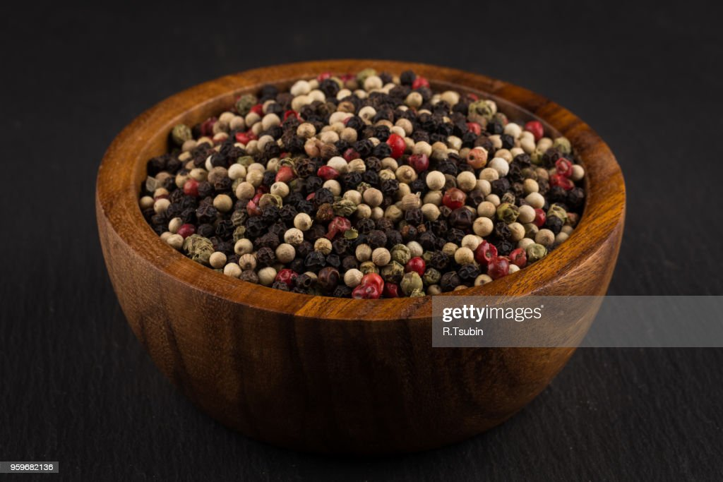 bowl of various pepper peppercorns seeds mix on black stone : Stock-Foto