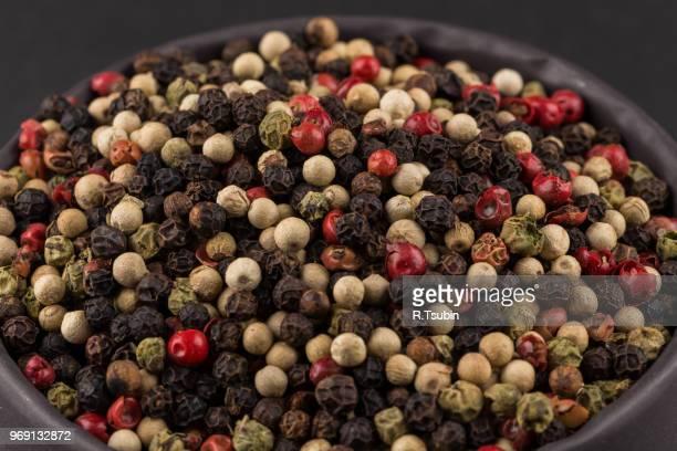 bowl of various pepper peppercorns seeds mix on dark stone