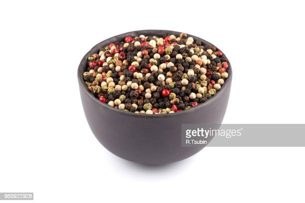 bowl of various pepper peppercorns seeds mix on white