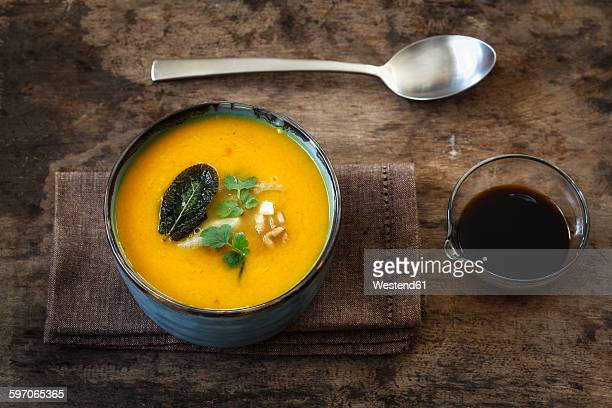 bowl of vegan creamed pumpkin soup with walnuts and soy sauce - soy sauce stock photos and pictures