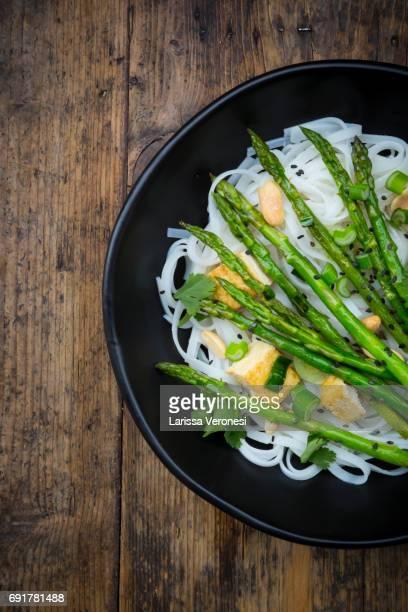 bowl of vegan Pad thai with mini green asparagus and tofu