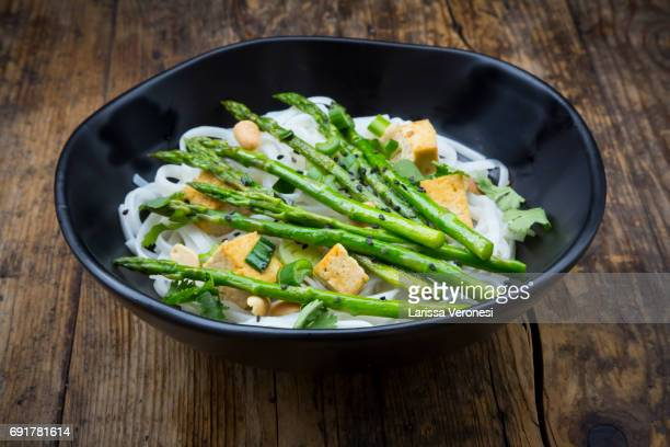 bowl of vegan Pad thai with mini green asparagus and tofu