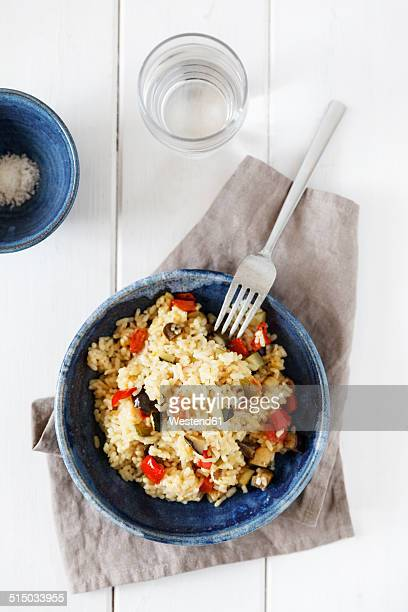 Bowl of vegetable paella, fork and glass of water, elevated view