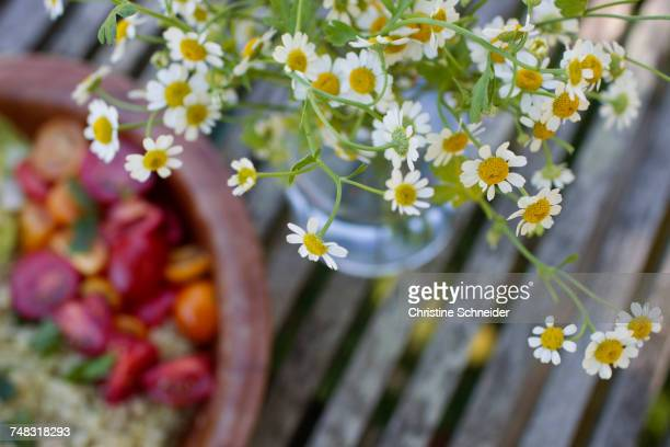 Bowl of vegetarian food by camomile flowers