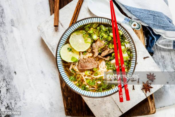 bowl of vietnamese pho with rice noodles, mung beans, cilantro, spring onions and limes - スターアニス ストックフォトと画像