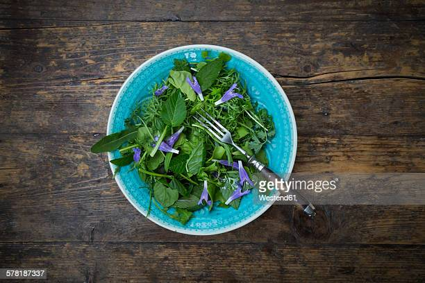 Bowl of wild-herb salad with edible flowers