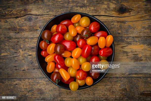 Bowl of yellow and red mini tomatoes on wood
