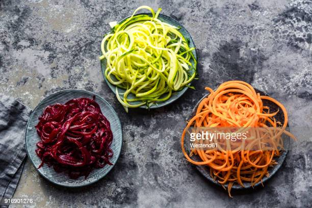 bowl of zoodles and bowls of carrot and beetroot spaghetti - zucchini stock pictures, royalty-free photos & images