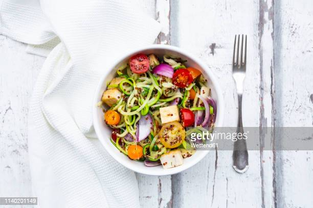bowl of zoodles with fried tofu, red quinoa, red onions and tomatoes - low carb diet stock photos and pictures