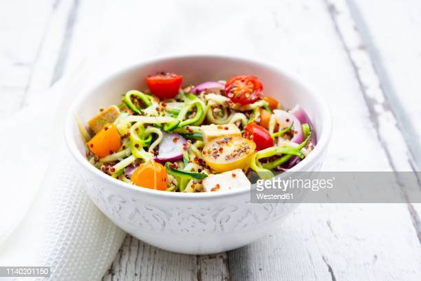Bowl of zoodles with fried tofu, red quinoa, red onions and tomatoes