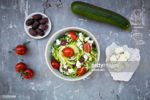 Bowl of zucchini spaghetti with feta, cherry tomatoes and black olives